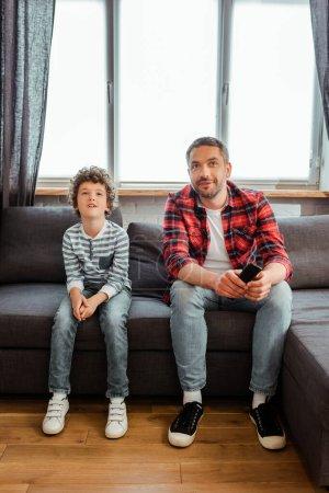 Photo pour Beau père et bouclé fils regarder film dans le salon - image libre de droit