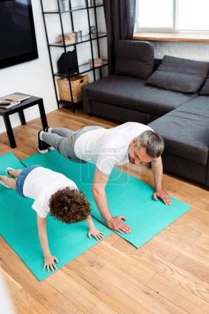 bearded father and curly son working out on fitness mats