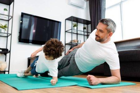 Photo pour Beau père et mignon fils exerçant sur tapis de fitness - image libre de droit