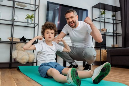 Photo for Happy father cheering near curly son showing muscle - Royalty Free Image