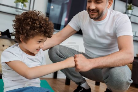 Photo for Cheerful father bumping fists with smiling son at home - Royalty Free Image