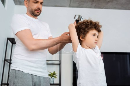 handsome father touching dumbbell while curly son exercising at home
