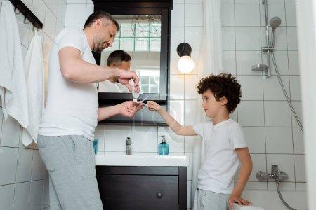 przystojny ojciec trzymając pastę do zębów w pobliżu szczoteczki kręcone syn