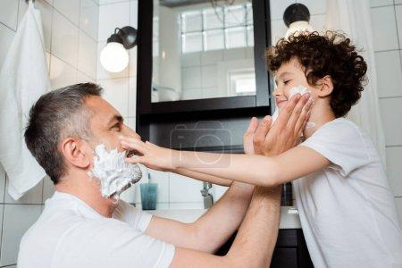 Photo pour Vue latérale du père heureux et mignon fils avec mousse à raser toucher les visages dans la salle de bain - image libre de droit