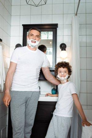 Photo pour Heureux père et fils bouclé avec mousse à raser sur les visages regardant caméra dans la salle de bain - image libre de droit