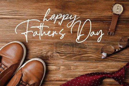 Photo pour Vue du dessus de chaussures décontractées hommes beige, cravate rouge à pois, montre-bracelet et lunettes sur fond en bois, illustration heureuse de la fête des pères - image libre de droit