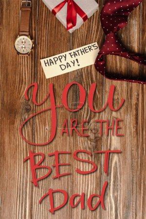 Photo pour Top vue de boîte cadeau avec arc rouge, carte de voeux avec lettrage heureux jour des pères et hommes cravate rouge et montre-bracelet sur fond en bois, vous êtes la meilleure illustration papa - image libre de droit