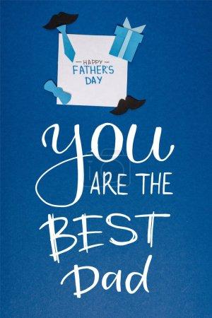 Photo pour Vue du haut de la carte de vœux avec lettrage heureux jour des pères et papier artisanat éléments de décoration créatifs sur fond bleu, vous êtes la meilleure illustration papa - image libre de droit