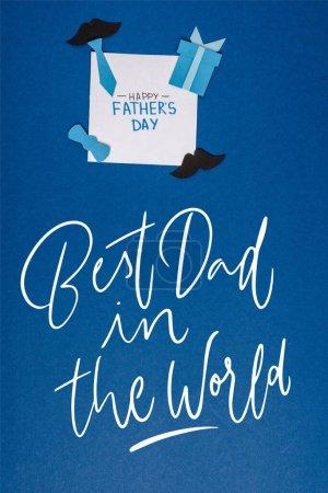 Photo pour Vue du haut de la carte de vœux avec lettrage heureux jour des pères et papier artisanat éléments de décoration créatifs sur fond bleu, meilleur papa dans l'illustration du monde - image libre de droit