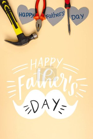 Photo for Top view of hammer, screwdriver, pliers and grey paper hearts on beige background, happy fathers day illustration - Royalty Free Image
