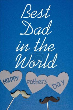 Photo pour Vue du dessus de moustache noire décorative et de papier découpé coeurs gris avec lettrage heureux jour des pères sur fond bleu, meilleur papa dans l'illustration du monde - image libre de droit