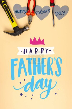 top view of hammer, screwdriver, pliers and grey paper hearts on beige background, happy fathers day illustration