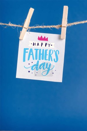White paper with happy fathers day illustration hanging on rope with clothespins isolated on blue