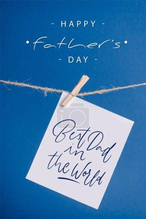 Photo pour Carte de vœux blanche avec le meilleur papa du monde illustration accrochée à une corde avec des pinces isolées sur bleu - image libre de droit