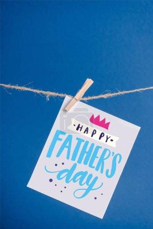 Photo pour Carte de vœux blanche avec illustration heureuse de la fête des pères accrochée à une corde avec des pinces isolées sur du bleu - image libre de droit