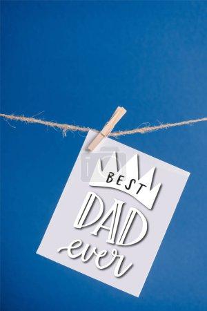 Photo pour Carte de vœux blanche avec le meilleur papa jamais illustration accrochée à une corde avec des pinces à linge isolées sur bleu - image libre de droit