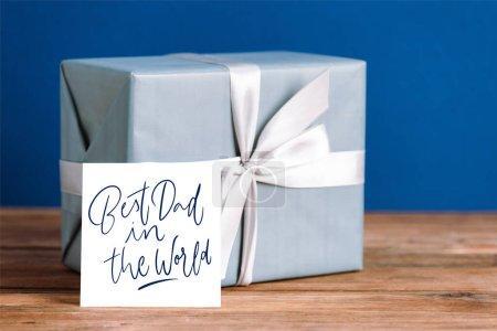 Photo pour Foyer sélectif de la carte de vœux avec le meilleur papa dans l'illustration du monde et boîte cadeau avec arc blanc isolé sur bleu - image libre de droit