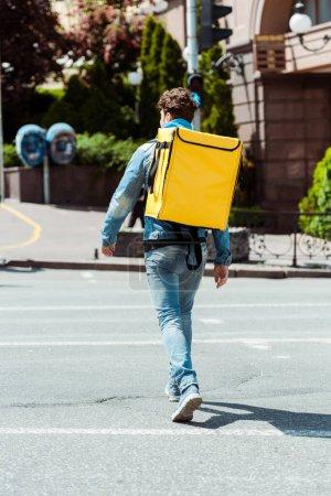Photo pour Vue arrière du messager avec sac à dos thermique marchant sur le passage supérieur - image libre de droit