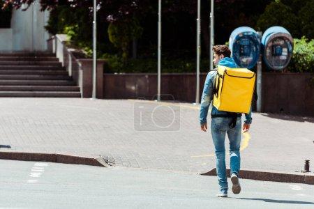 Photo pour Vue arrière du messager avec sac à dos thermique marchant sur le passage supérieur dans la rue urbaine - image libre de droit