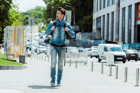 Photo for Delivery man with backpack walking on urban street near road - Royalty Free Image