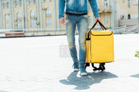 Photo for Cropped view of courier holding thermo bag on urban street at daytime - Royalty Free Image