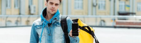 Photo pour Image horizontale du livreur avec sac thermique montrant un smartphone dans une rue urbaine - image libre de droit