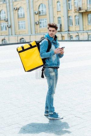 Foto de Vista lateral del repartidor con mochila térmica que sostiene el teléfono inteligente en la calle urbana - Imagen libre de derechos