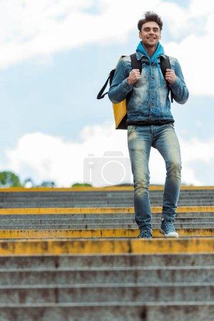 Foto de Vista de ángulo bajo del courier positivo con mochila térmica caminando por escaleras con cielo nublado a fondo. - Imagen libre de derechos