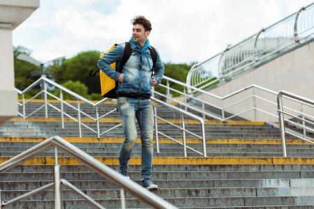 Photo pour Mise au point sélective du courrier souriant avec sac à dos thermique descendant les escaliers avec rampe - image libre de droit