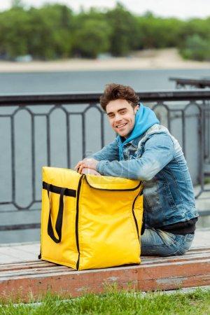 Photo pour Vue latérale du beau coursier souriant à la caméra près du sac thermo sur banc dans la rue urbaine - image libre de droit