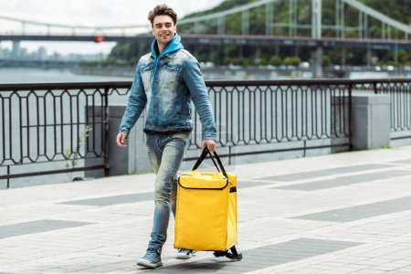 Smiling courier with thermo bag walking on promenade
