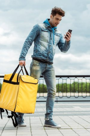 Photo for Smiling courier with thermal bag looking at smartphone on urban street - Royalty Free Image