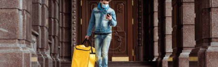 Photo for Panoramic crop of courier in medical mask holding thermo bag and using smartphone near building - Royalty Free Image