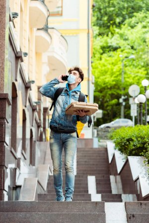 Courrier en masque médical parlant sur smartphone tout en tenant des boîtes à pizza près du bâtiment