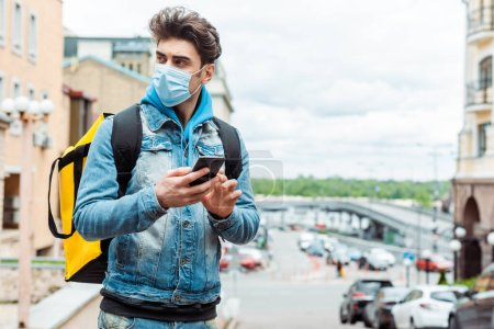 Delivery man in medical mask using smartphone near road on urban street