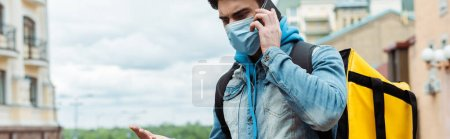 Panoramic orientation of courier in medical mask with thermo backpack pointing with hand and talking on smartphone on urban street