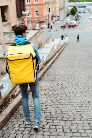 Photo pour Vue arrière du messager en masque médical avec sac à dos thermique marchant près de la rue urbaine - image libre de droit