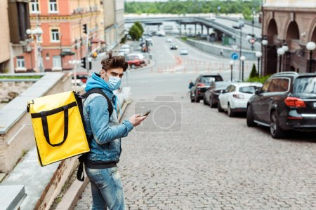 Photo for Side view of courier in medical mask with thermo backpack using smartphone on urban street - Royalty Free Image
