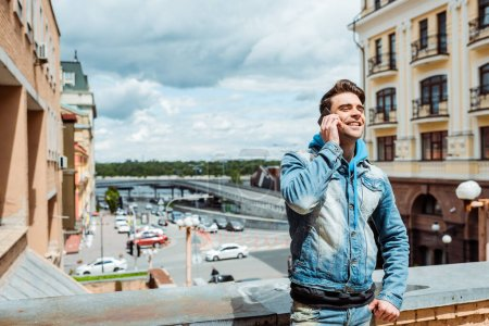 Handsome man smiling while talking on smartphone with cloudy sky and urban street at background