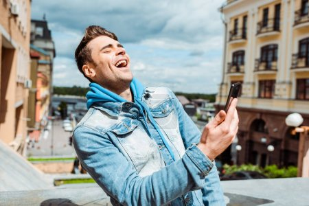 Handsome man laughing while holding smartphone on urban street