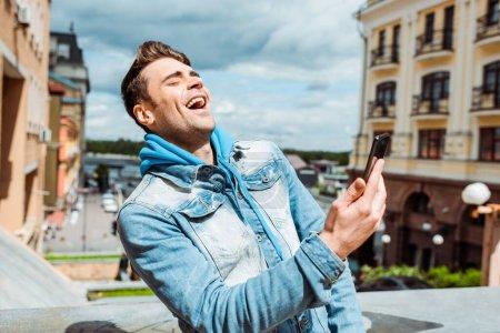 Photo pour Bel homme rire tout en tenant smartphone sur la rue urbaine - image libre de droit