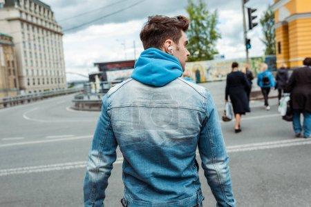 Photo pour Vue arrière de l'homme dans les écouteurs marchant sur le passage supérieur dans la rue urbaine - image libre de droit