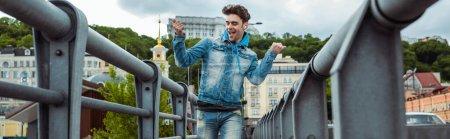 Photo pour Récolte panoramique de l'homme positif dans les écouteurs montrant geste ouais tout en marchant sur le pont - image libre de droit