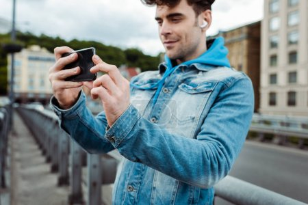 Photo pour Concentration sélective du bel homme dans les écouteurs prenant des photos avec smartphone sur la rue urbaine - image libre de droit