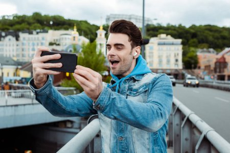 Existed young man in earphones taking picture with smartphone on bridge
