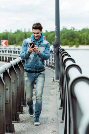 Photo for Selective focus of smiling man using smartphone while walking on bridge - Royalty Free Image