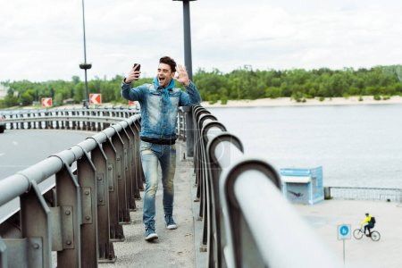Photo for Selective focus of cheerful man having video call on smartphone while walking on bridge - Royalty Free Image