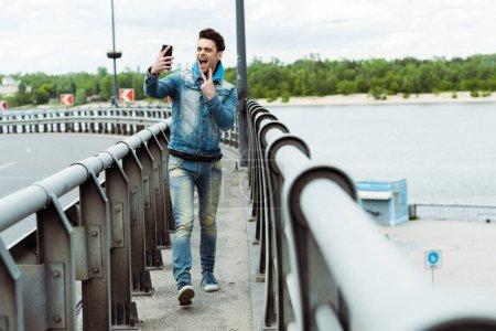 Photo pour Focus sélectif de l'homme joyeux montrant signe de paix tout en prenant selfie avec smartphone sur le pont - image libre de droit