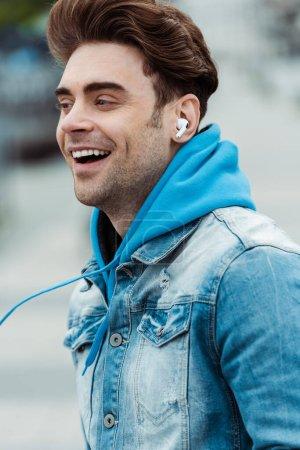 Photo pour Homme souriant dans les écouteurs regardant loin à l'extérieur - image libre de droit