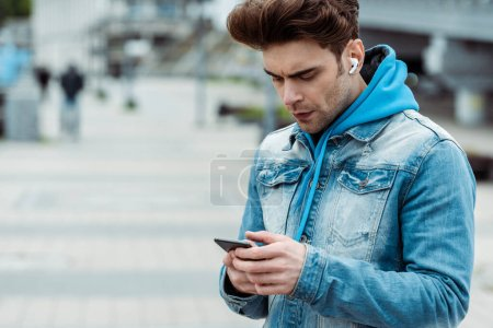 Handsome man in earphones using smartphone on urban street